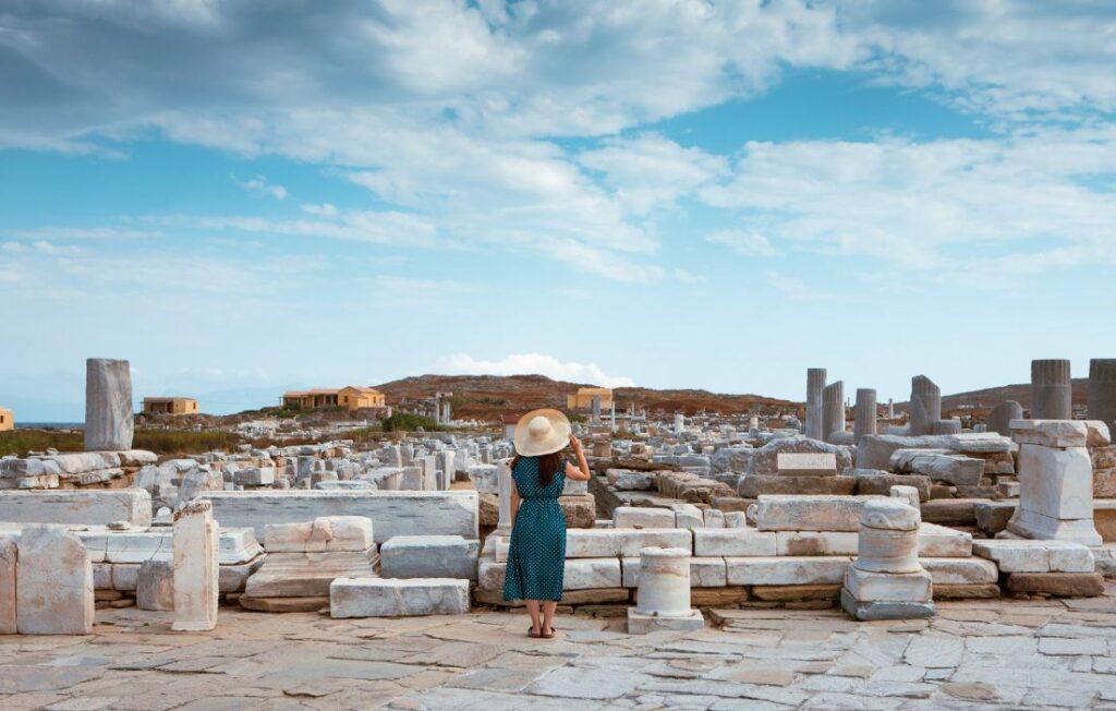 woman standing in front of Delos Greek Islands ruins