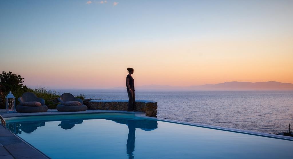 woman in Tinos island by the pool looking the sea