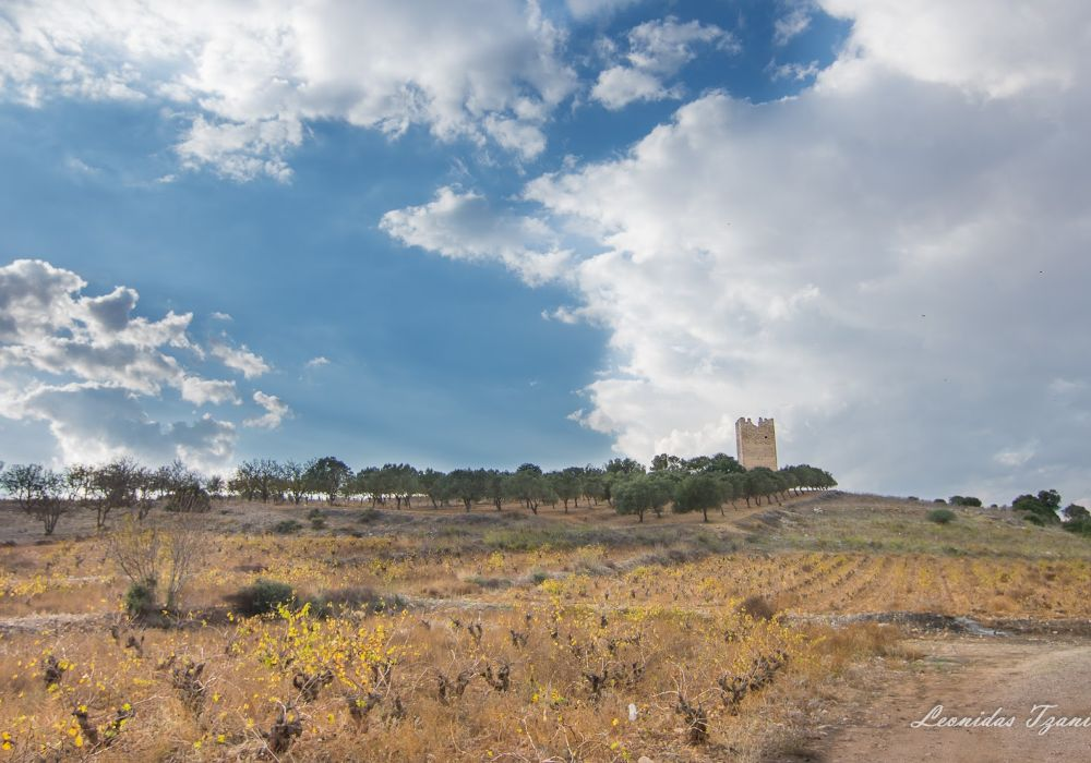 Tower of Vravrona surrounded by trees, fields and vineyards with cloudy sky