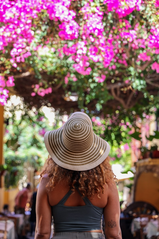 a woman standing in a busy road with bougainvillea in Greece